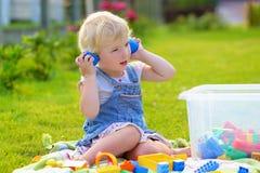 Förskolebarnflickan som spelar med plast-, blockerar utomhus Royaltyfri Fotografi