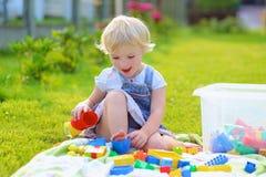 Förskolebarnflickan som spelar med plast-, blockerar utomhus Royaltyfria Foton