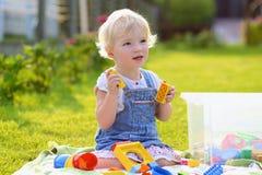 Förskolebarnflickan som spelar med plast-, blockerar utomhus Arkivfoton