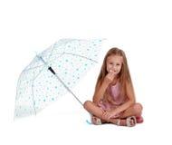 Förskolebarnunge som äter sötsaker Charmigt flickasammanträde med paraplyet som isoleras på en vit bakgrund Dagisbegrepp arkivbilder