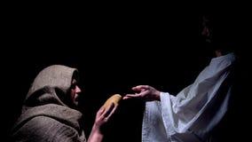 Förskoning Jesus i krona av taggar som ger bröd för den hungriga hemlösa mannen, mirakel fotografering för bildbyråer