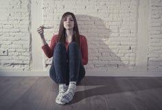 Förskräckt bekymrad gravid tonåringflicka eller hållande positiv graviditetstest för ung desperat kvinna Arkivbild