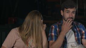 Förskräckt flicka som stänger henne ögon med hennes händer som håller ögonen på läskig film i bion Fotografering för Bildbyråer