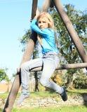 Förskräckt flickasammanträde på klättringram Arkivfoton