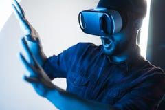 Förskräckt grabb i VR-exponeringsglas som undersöker cyberspace arkivfoto