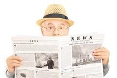 Förskräckt hög man med exponeringsglas som döljer bak en tidning Arkivfoton