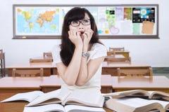 Förskräckt kvinnligt elevsammanträde i klassrumet Royaltyfria Foton