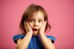 Förskräckt liten flicka med den öppna munnen för sned boll och stora ögon royaltyfri foto
