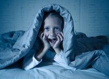 Förskräckt liten flickabeläggningframsida med händer i skräck i mörker på natten royaltyfri foto