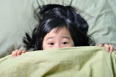 Förskräckt litet asiatiskt flickanederlag bak filten Royaltyfri Fotografi