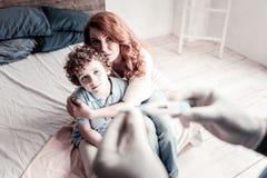 Förskräckt moder som dåligt oroar om hennes son Arkivfoto