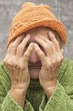 Förskräckt och bekymrad äldre kvinna Arkivfoto