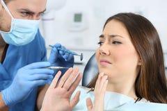Förskräckt patient i ett tandläkarekontor fotografering för bildbyråer