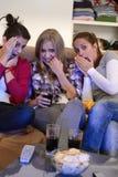 Förskräckt flickor som håller ögonen på fasafilm på televisionen Arkivbild
