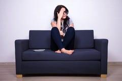 Förskräckt ung kvinna i exponeringsglas som 3d håller ögonen på tv Arkivfoton
