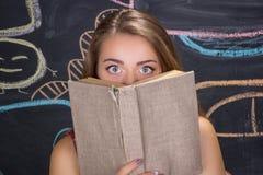 Förskräckta ögon av det unga studentflickanederlaget bak en bok Royaltyfria Foton