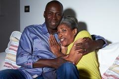 Förskräckta par på Sofa Watching TV tillsammans Arkivbilder