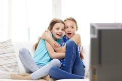 Förskräckta små flickor som hemma håller ögonen på fasa på tv arkivfoto