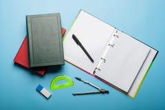 Förskriftsbok, böcker, penna och linjal på blå bakgrund royaltyfria foton