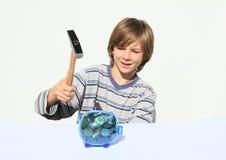 Förstörande besparingsvin för pojke mycket av pengar med hammaren Arkivbild