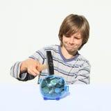 Förstörande besparingsvin för pojke mycket av pengar med hammaren Royaltyfri Foto