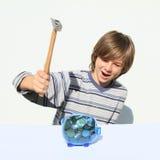 Förstörande besparingsvin för pojke mycket av pengar med hammaren Royaltyfria Bilder