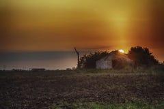 Förstörd byggnad med soluppgång på ängen royaltyfri fotografi