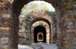 Förstörd korridor för gammal korridor för murverk för tegelstenbåge lång mörk under Royaltyfria Bilder