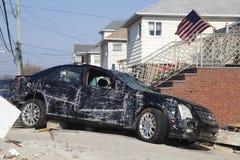Förstörd lyxig bil i efterdyningen av orkanen som är sandig i avlägsna Rockaway, New York Arkivbild