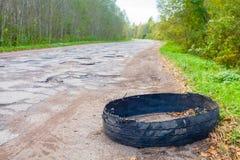 Förstörd rubber bil för bilgummihjul på den lantliga gropiga brutna vägen Royaltyfri Fotografi
