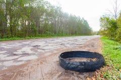 Förstörd rubber bil för bilgummihjul på den lantliga gropiga brutna vägen Arkivfoto