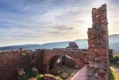 Förstörd slott på berget på solnedgången royaltyfria bilder