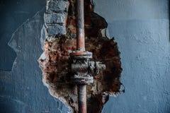 Förstörd vägg med en tegelsten Arkivfoton