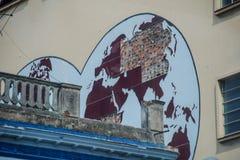 Förstörd världskarta på väggen av ett hus i havannacigarr arkivbild