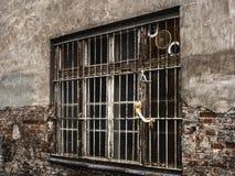 förstört fönster med stänger och en vägg royaltyfria bilder