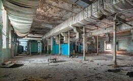 Förstört produktionrum av en gammal övergiven textilfabrik Arkivbilder