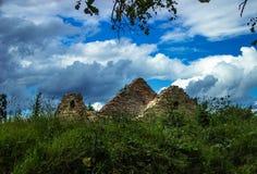 Förstört stenhus i ett fält utanför staden på den blåa himlen w Arkivbild