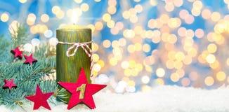 Första advent, adventgarnering, stearinljus och stjärna i snön Arkivfoton