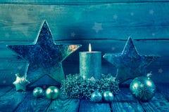 Första advent: en brinnande guld- stearinljus på en träbakgrund Royaltyfria Bilder