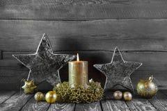 Första advent: en guld- bränningstearinljus på trä för garneringar Arkivfoto