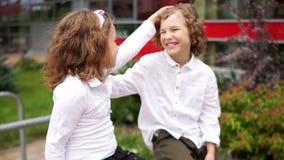 första förälskelse Flickan och pojken pratar glatt Flickan slår pojken på huvudet, pojkeskratten arkivfilmer