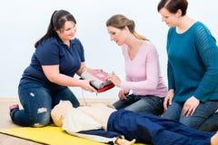 Första hjälpendeltagare i utbildning som lär att använda defibrillatoren för reanimation arkivbilder