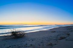 Första ljus av dagen på en klar morgon på stranden av Valencia Magisk blåaktig soluppgång med bakgrund för orange glöd royaltyfria foton