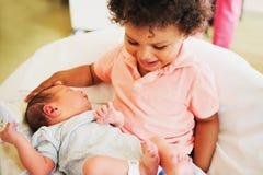 Första möte av den förtjusande afrikanska litet barnpojken och hans nyfödda broder Royaltyfria Foton