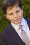 Första nattvardsgångklänning för pojke som ler till kameran Fotografering för Bildbyråer