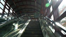 Första-person sikt av rulltrappan som flyttar sig upp på en solig dag arkivfilmer