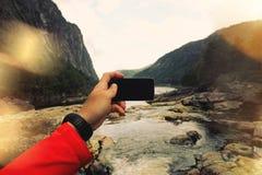 Första-personen sikten, mannen tar ett foto av en bergflod på smartfon Begrepp svartskärmsmartphone Arkivfoto