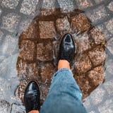 Första personpunkt av siktskvinnamomentet in i pöl i svarta skor arkivbild