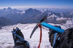 Första personsikt som förkroppsligar, och avlägset landskap Manben i isbroddar med en isyxa tar en vila på överkanten av berget Arkivfoton