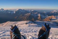 Första personsikt som förkroppsligar, och avlägset landskap Manben i isbroddar tar en vila på överkanten av berget Fot, i trekkin Arkivfoto